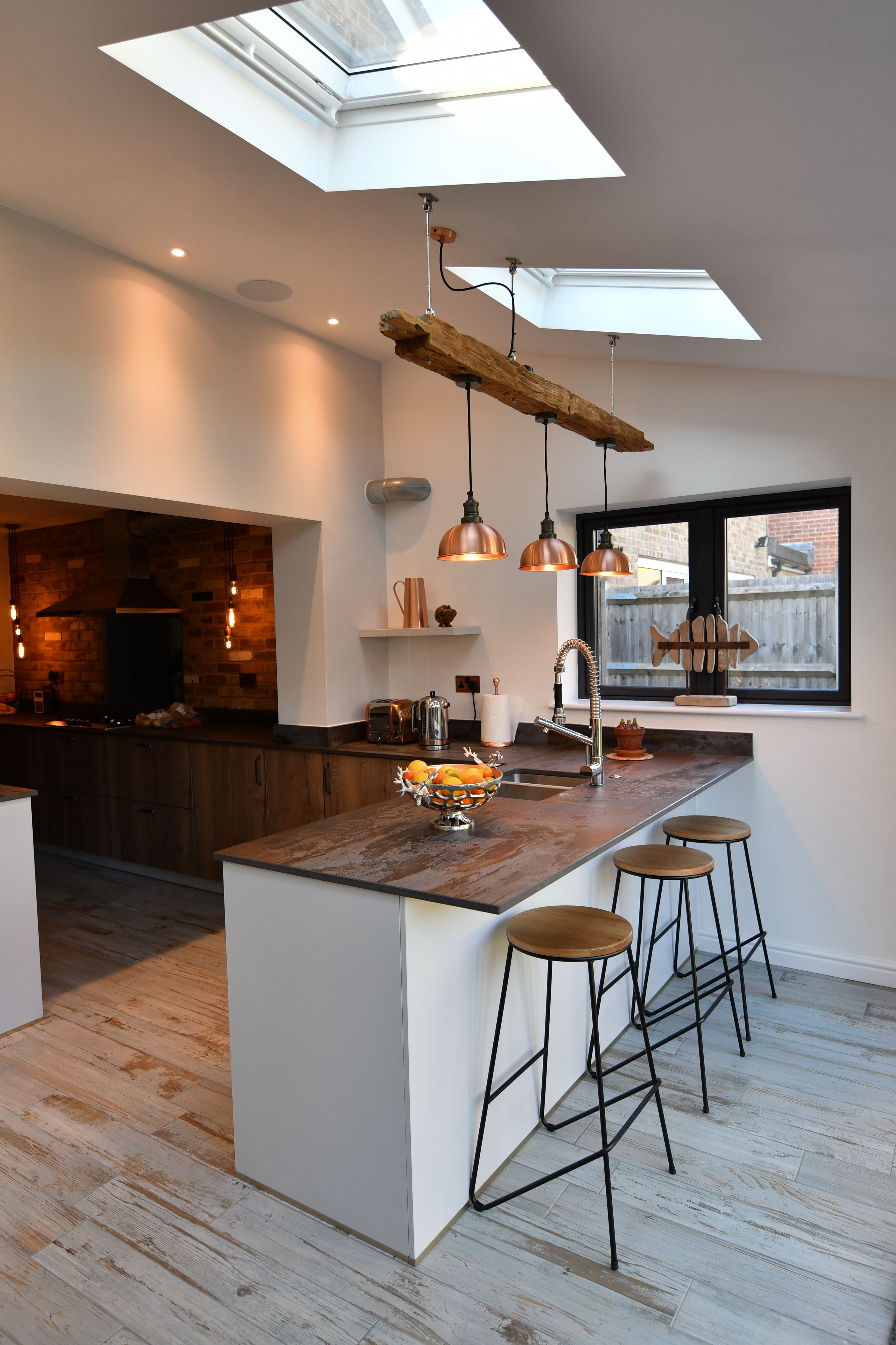 A trio of lights above a kitchen counter make for the perfect statement how incredible do these lights look embedded into a panel of wood