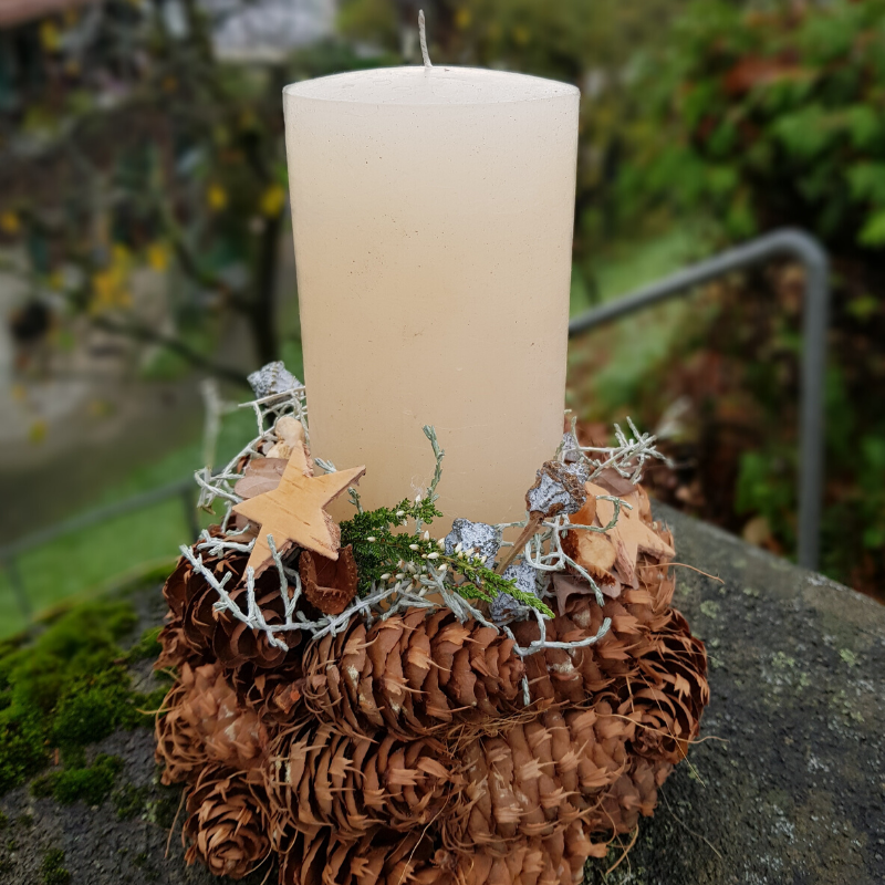 Photo of Candle decoration with pine cones