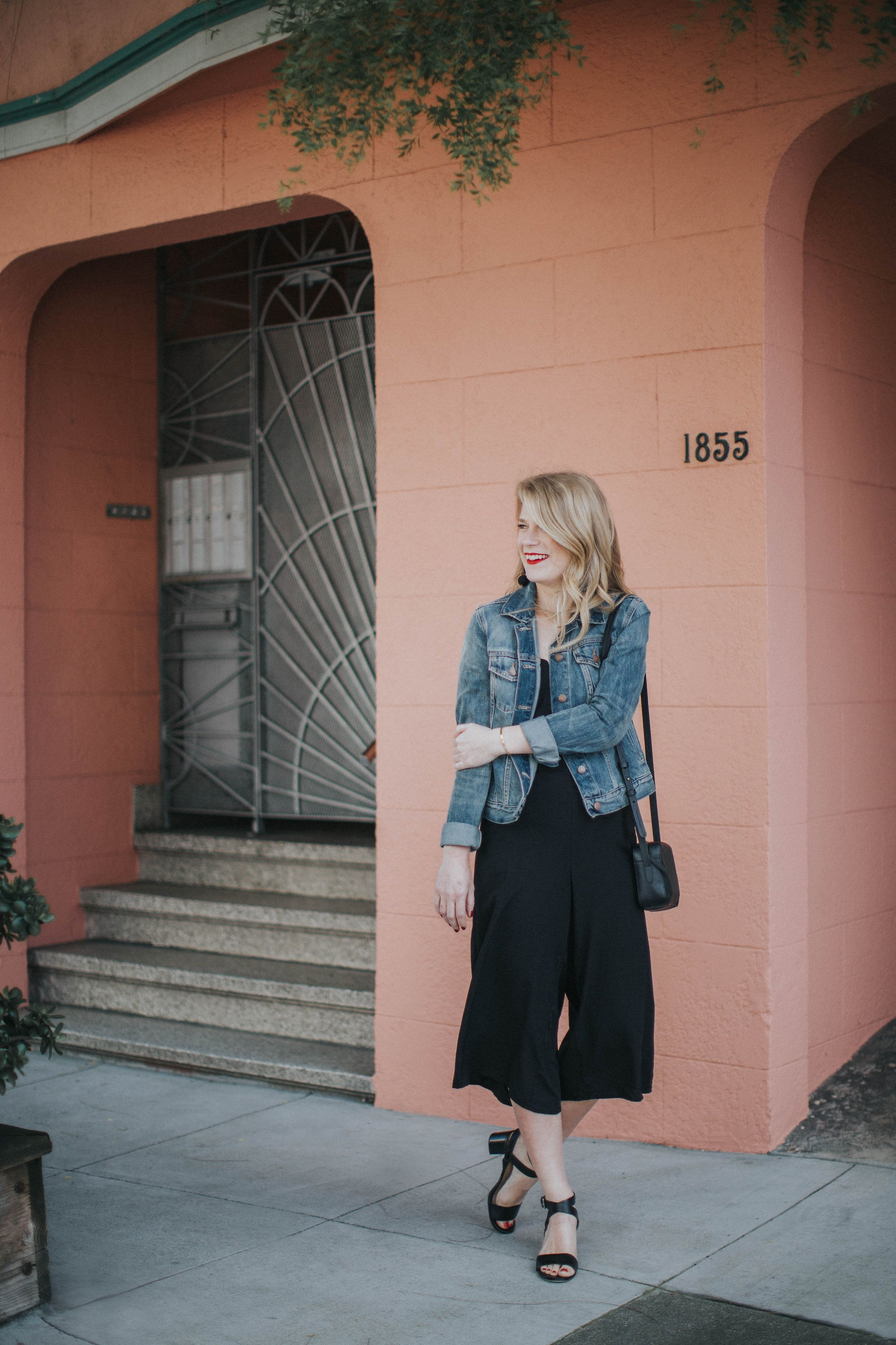f2a4f46699c Blogger Cait Weingartner of Pretty   Fun wearing Old Navy culotte jumpsuit  with M. Gemi sandals and a GAP denim jacket.