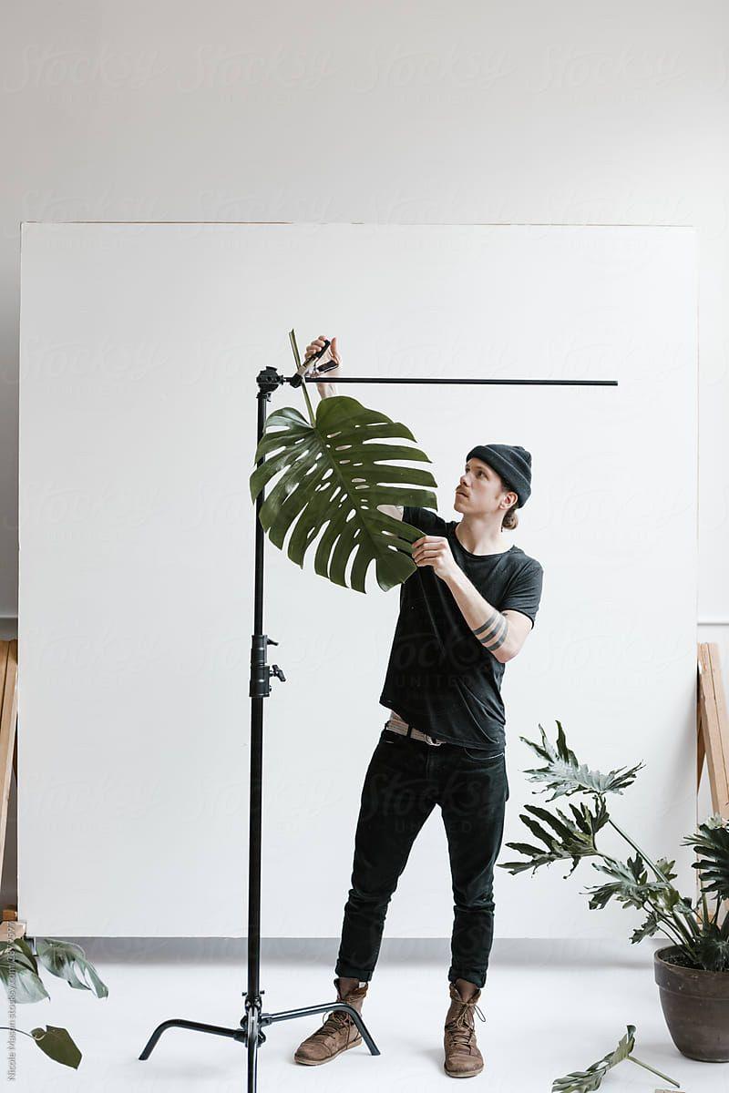 junger Mann, der Pflanzenstützen im Fotostudio von Nicole Mason für Stocksy United aufbaut