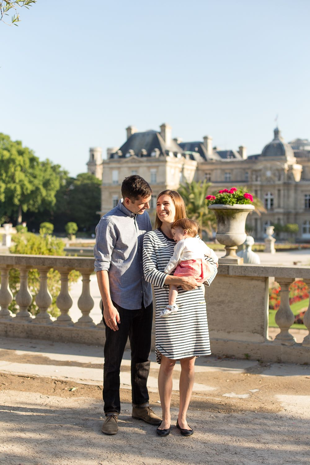 Beautiful family in Paris  Mom and Dad smile at each other while their daughter laughs at the Chateau de Louvre by Family and Maternity Photographer, Katie Donnelly