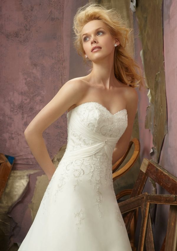 A strapless, slim A-line gown with a corset back has a beaded ...