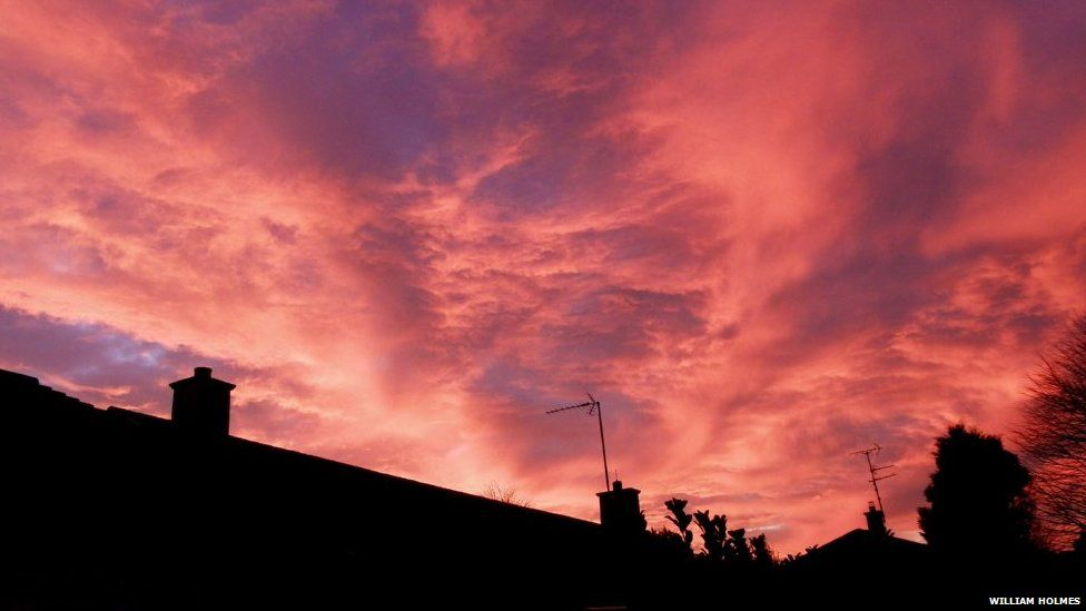 A red-hued sky fills the photo. There are patches of blue sky peeking from underneath. A house and a tree is in silhouette across the bottom of the photo.