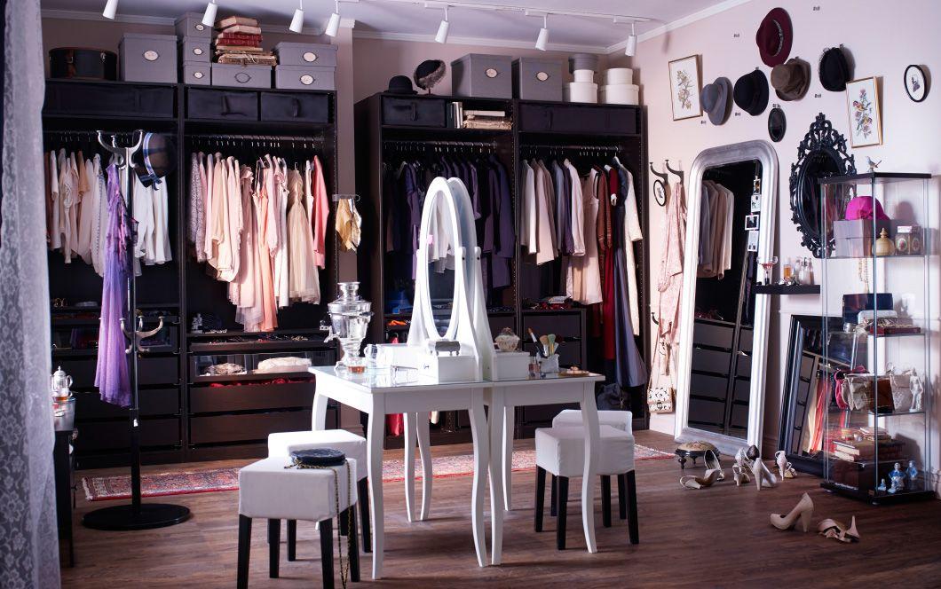 Pohľad na celú miestnosť s toaletnými stolíkmi, veľkým zrkadlom a otvorenými šatníkmi.