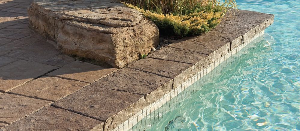 square paver natural stone coping around pool with paver deck
