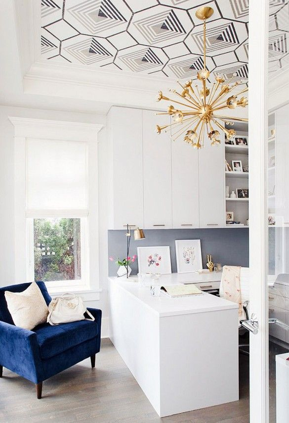 Modern office with white built-ins, wallpapered ceiling, blue velvet chair, and dramatic gold light fixture