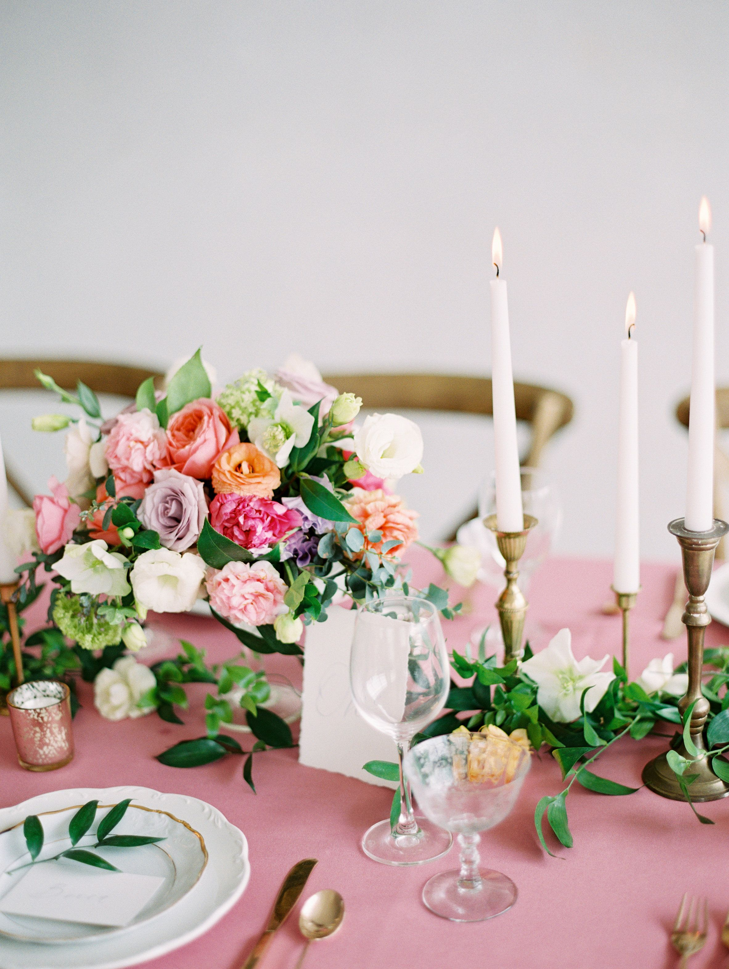 Colorful tablescape of pinks, purples, peaches and greenery with ...