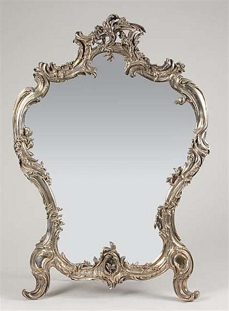 <b>Louis XV Style Silvered Metal Dressing Table Mirror </b></i> <br /> Sormani, Paris <br /> Of cartouche form, decorated with rocaille motifs, on scrolling feet, easel back. <i>Height 27 inches.</b></i>