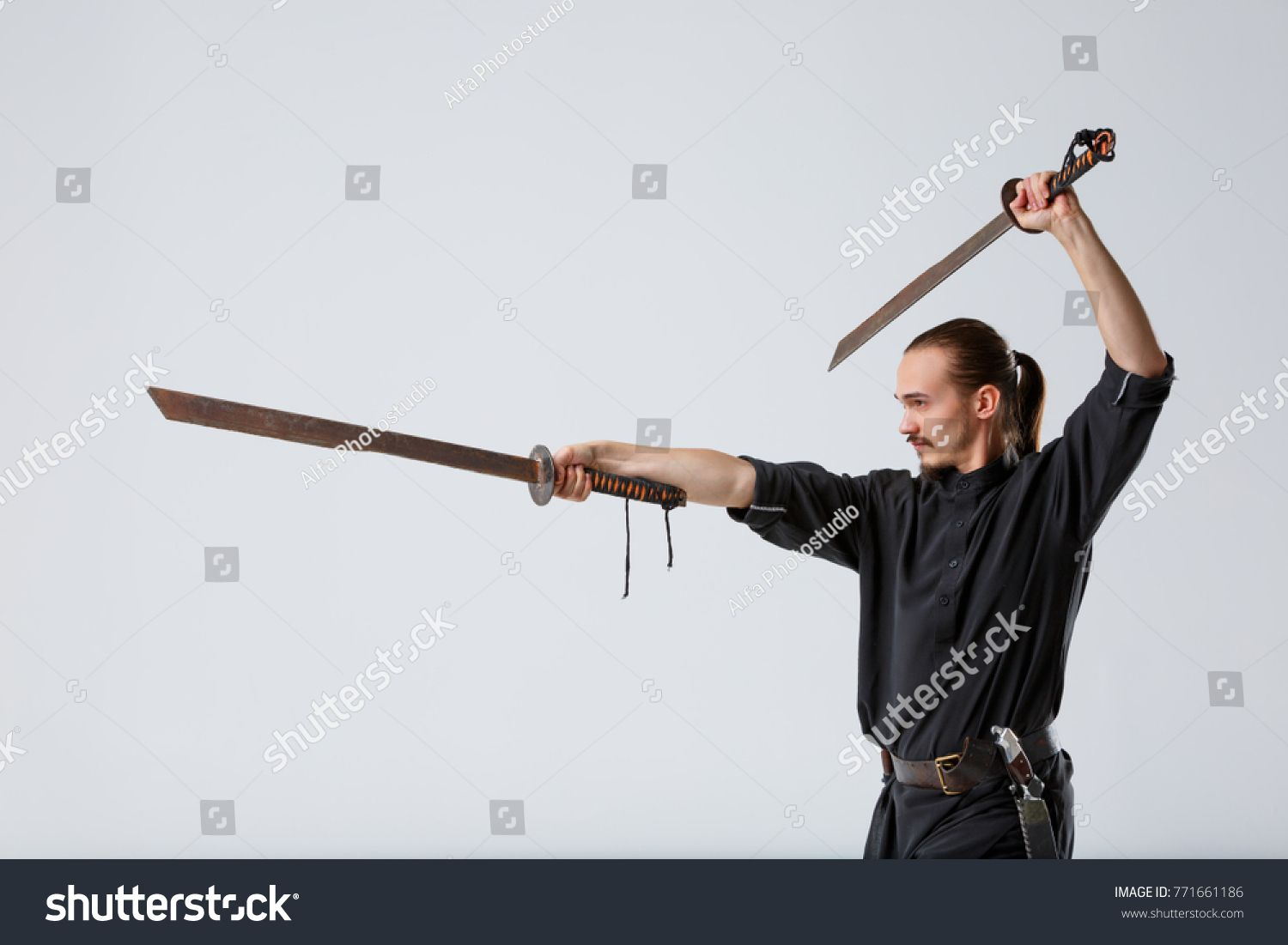 Stock Photo A Ninja Man Stands Sideways With Swords In A Fighting