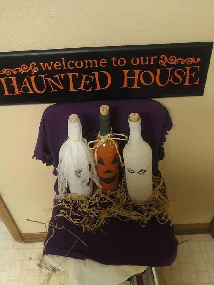 DIY Halloween Decor! Halloween vinyl saying put on painted black board. Wine bottles turned into ghosts & pumpkin; faces using vinyl Halloween embellishments