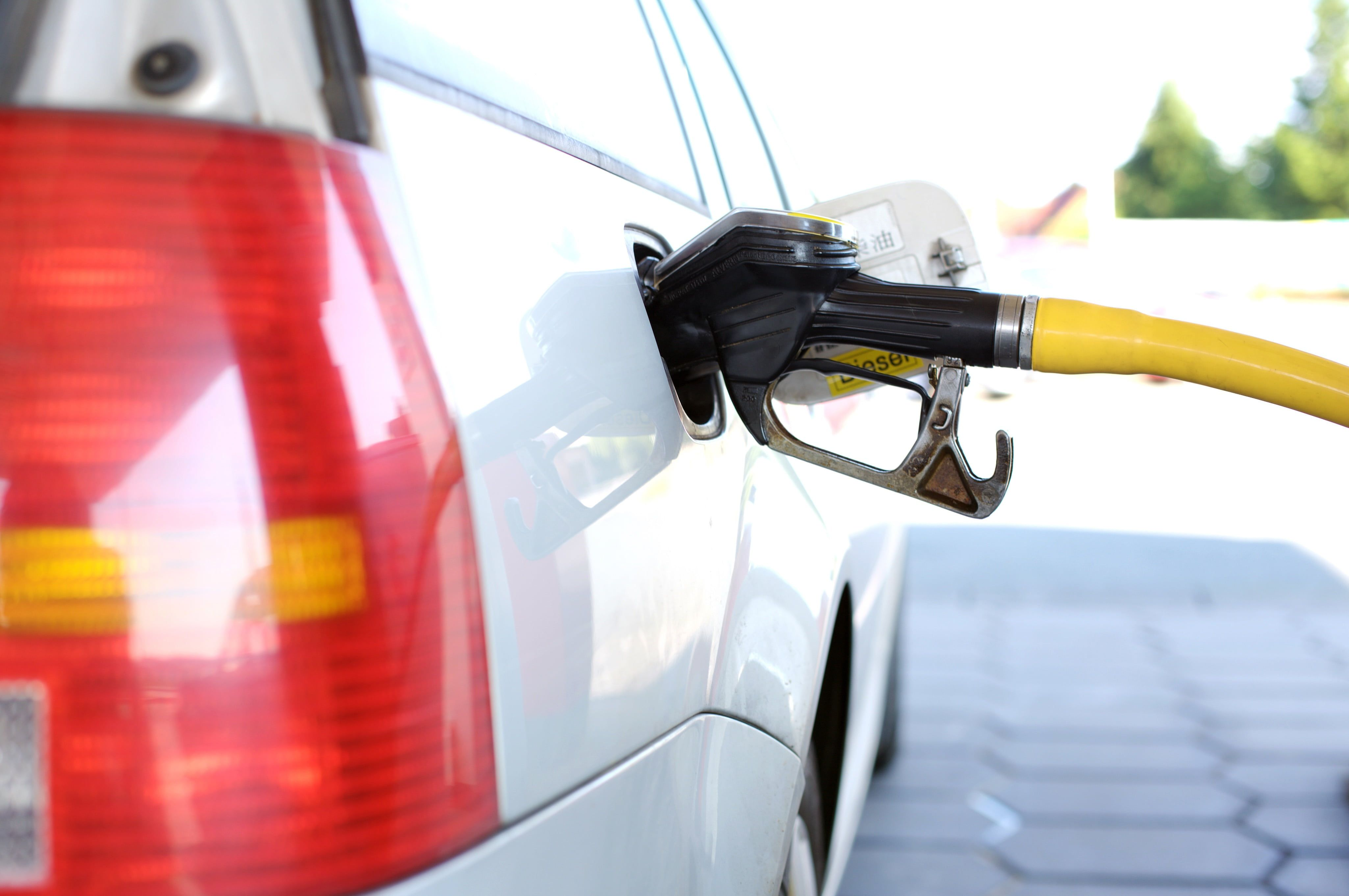 White Vehicle Filling Gas Tank Using Gasoline Pump Refuel