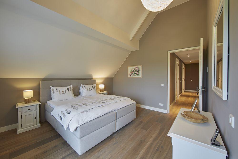 De ruime slaapkamer heeft taupe muren en een rustieke houten vloer ...