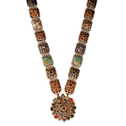A Necklace with Navaratna Stones  North India or Hyderabad  Late 18th early 19th Century    A magnificent necklace from North India or Hyderabad. The central pendant with two layers of navaratna stones (nine Holy Stones) hanging from a necklace of linked navaratna squares separated with five lines of natural pearls.    The reverse has magnificent enamelling.