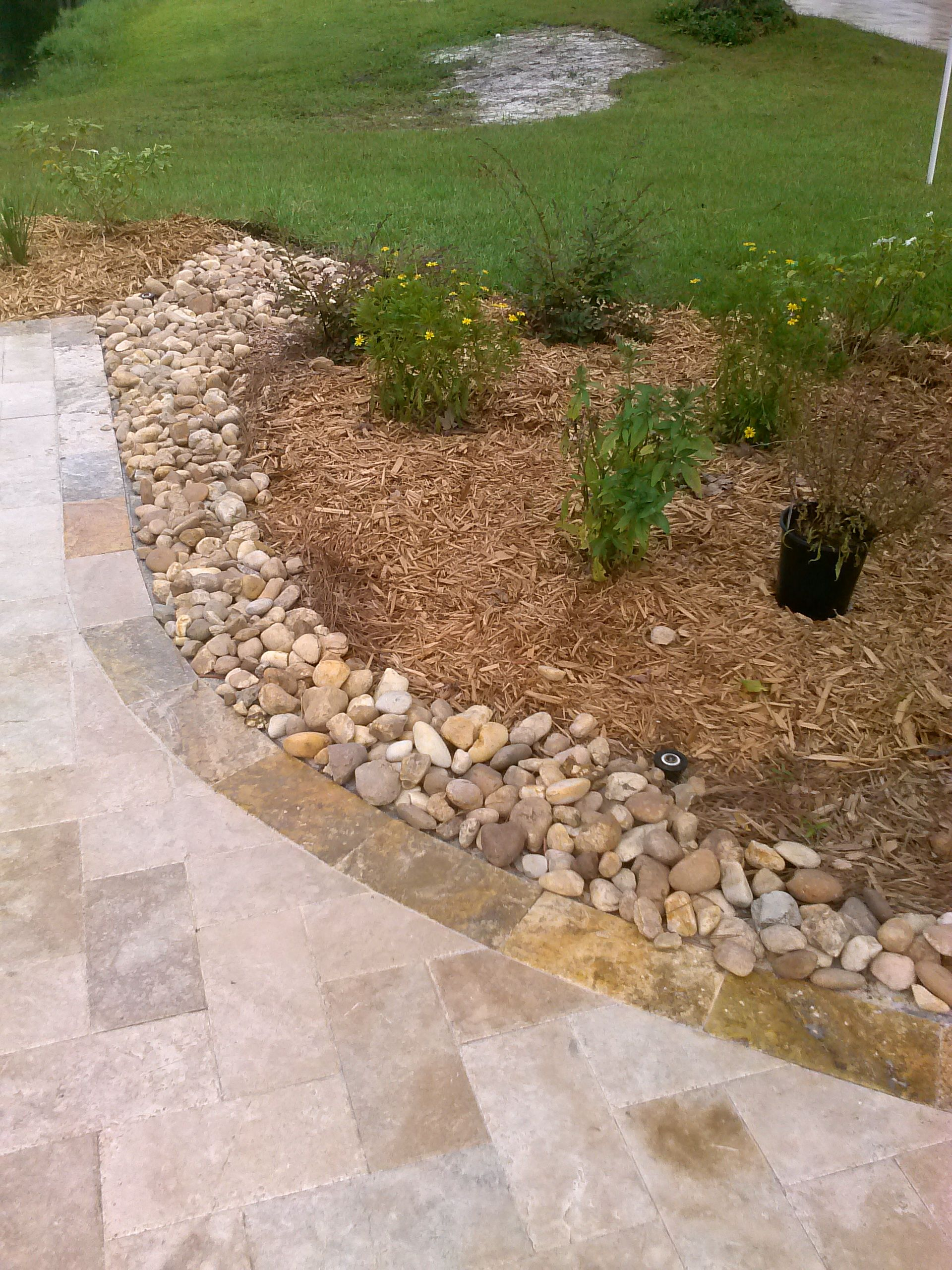 Using river rock as a driveway landscape border to stop rainwater from washing the mulch away