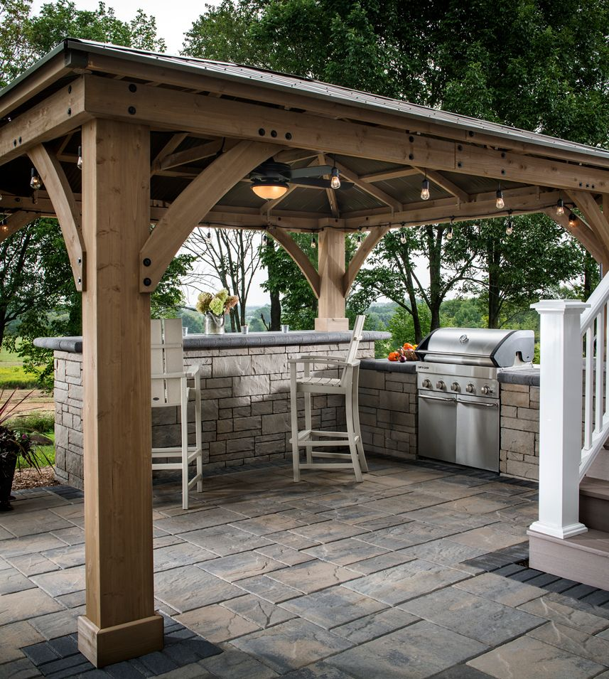This Outdoor Kitchen Feature A Bar For Seating And A Contemporary Grill Island The Wood Pergola Adds Extra Protec Backyard Patio Pergola Outdoor Grill Station