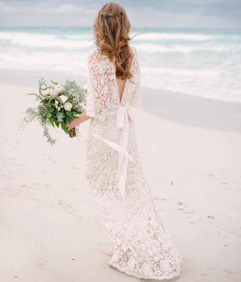 Love the '60s-inspired styling of this wedding dress with its long bell sleeves and dramatic train lends the gown a laid-back bohemian feel, while a plunging neckline and low back offer up just the right amount of sex appeal.