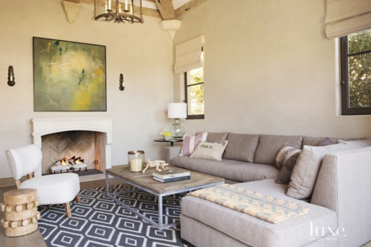 In the family room, a custom sectional wrapped with a Perennials outdoor chenille from David Sutherland is paired with a coffee table from Juxtaposition Home. A West Elm rug lends dimension to the space; the mixed-media piece is from Bassman Blaine.
