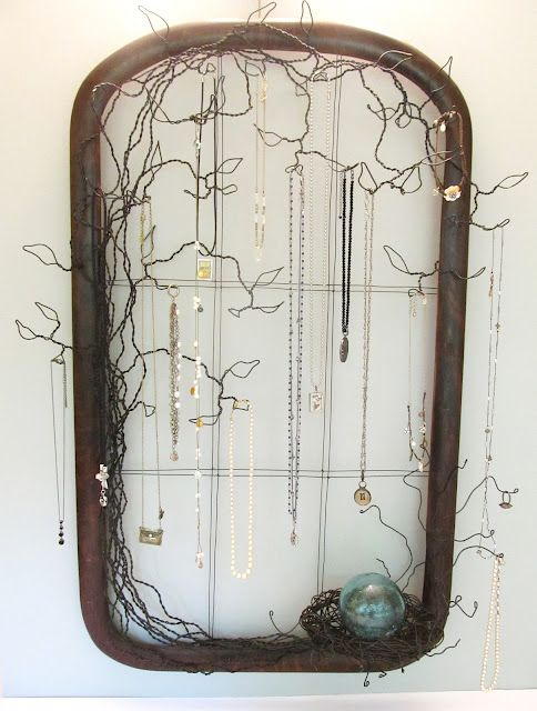Sassytrash jewelry holderL: looks like a frame with an overlay of black wire formed into tree branches and leaves, from which many things can be dangled.