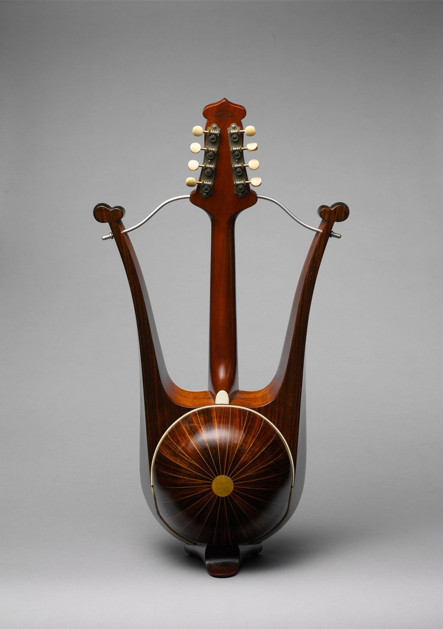 """""""This unusual instrument evokes the form of the classical Greek lyre with the body of a mandolin. The design was patented by Turturro in 1904 and was produced by at least one other maker. The top is punctuated by two unusual oval sound holes, and the back has a hemispherical bowl of twenty-four ribs."""""""