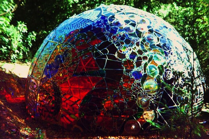 """Artist Carol Geary, aka Caroling, conceived, built, and completed this incredible stained glass dome, entitled Wholeo Dome (pronounced """"Holy O""""), in 1974. When creating the piece, Caroling said, """"I wanted not to look at a window, but to be in a window."""" So, many trials and shattered pieces of glass later, the 14-foot wide, 7-foot tall dome was constructed."""