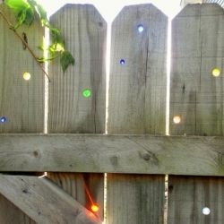 Press marbles into holes in a fence for a sparkling light show when the sun hits the color. DIY tutorial via gardendrama.wordpress.com