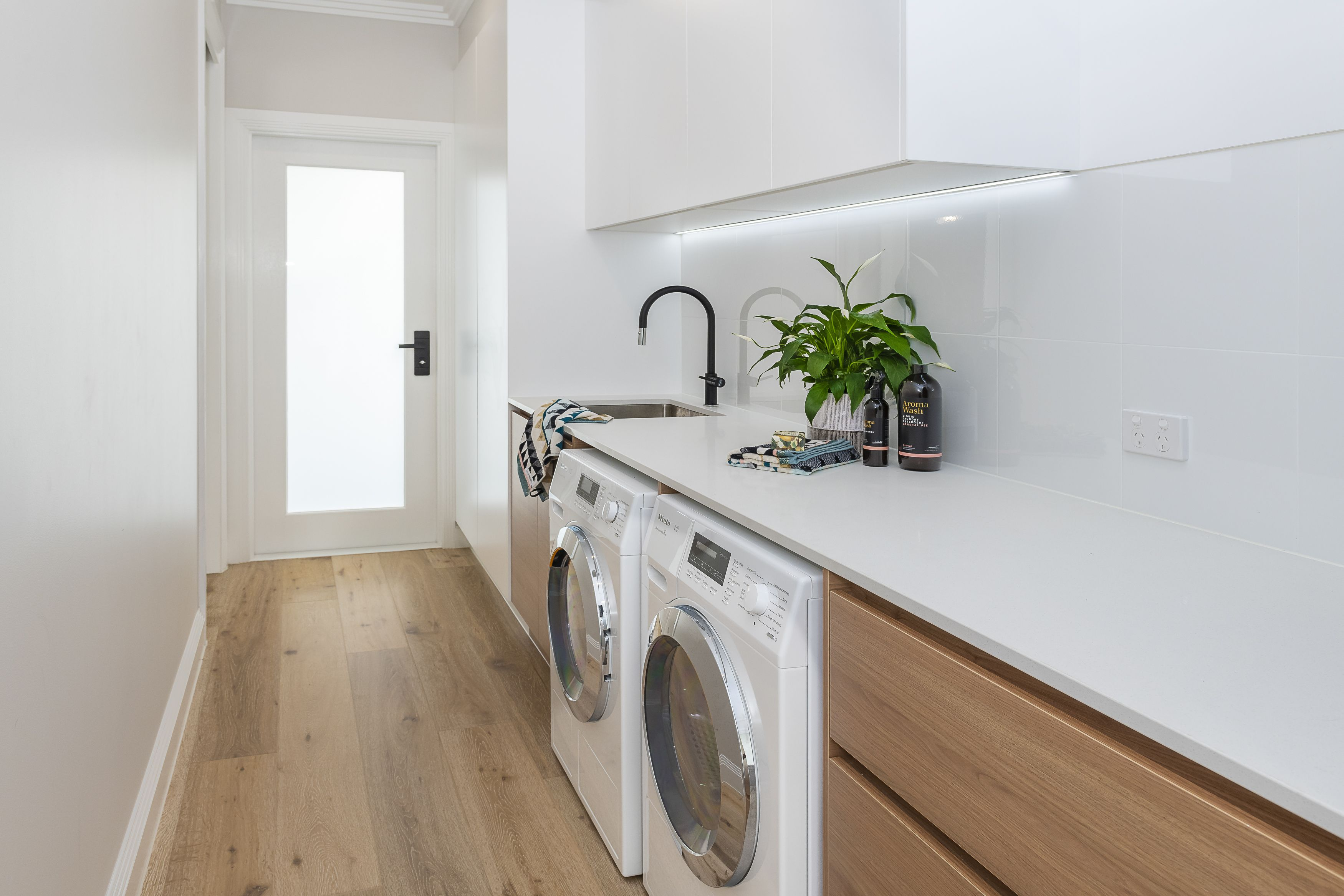 White and timber galley laundry with strip lighting and black