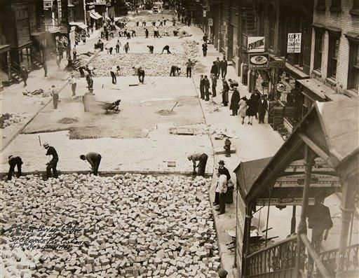 In this Oct. 2, 1930 photo provided by the New York City Municipal Archives, workers assemble bricks to build the roadway on 28th Street in New York.