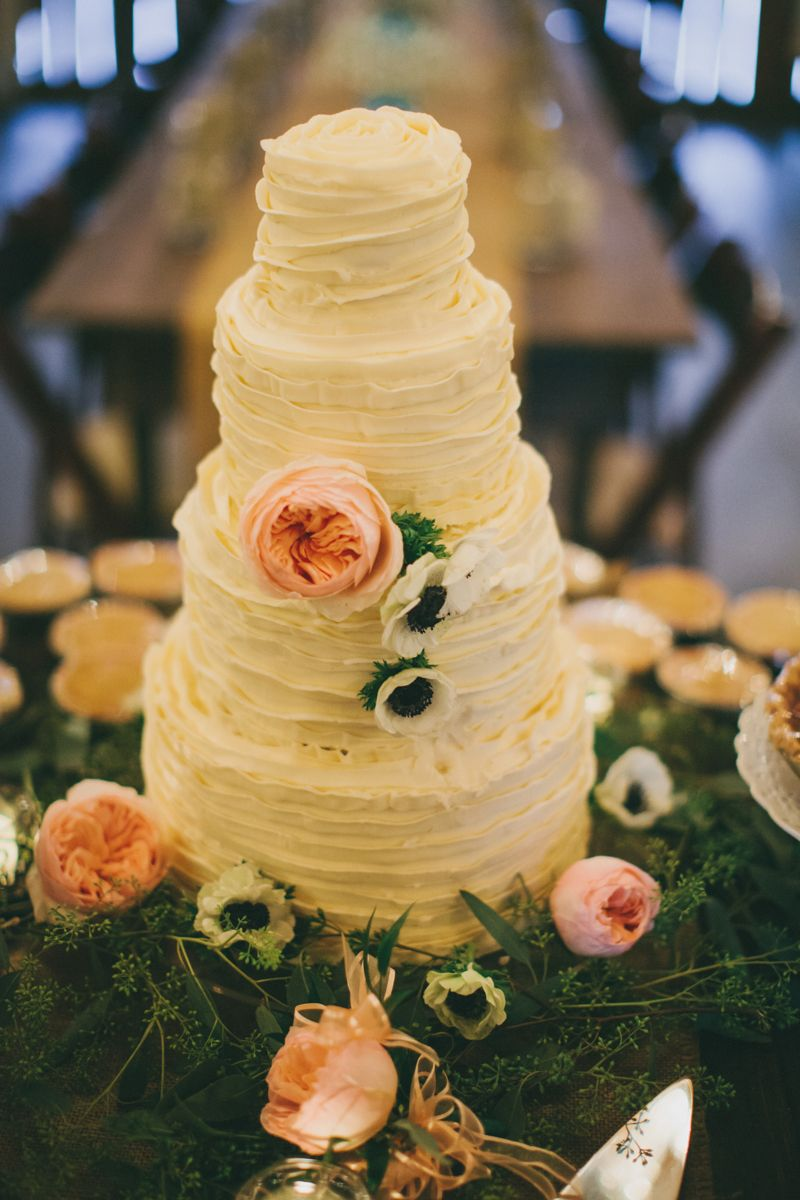 Ruffled wedding cake decorated with fresh flowers wedding