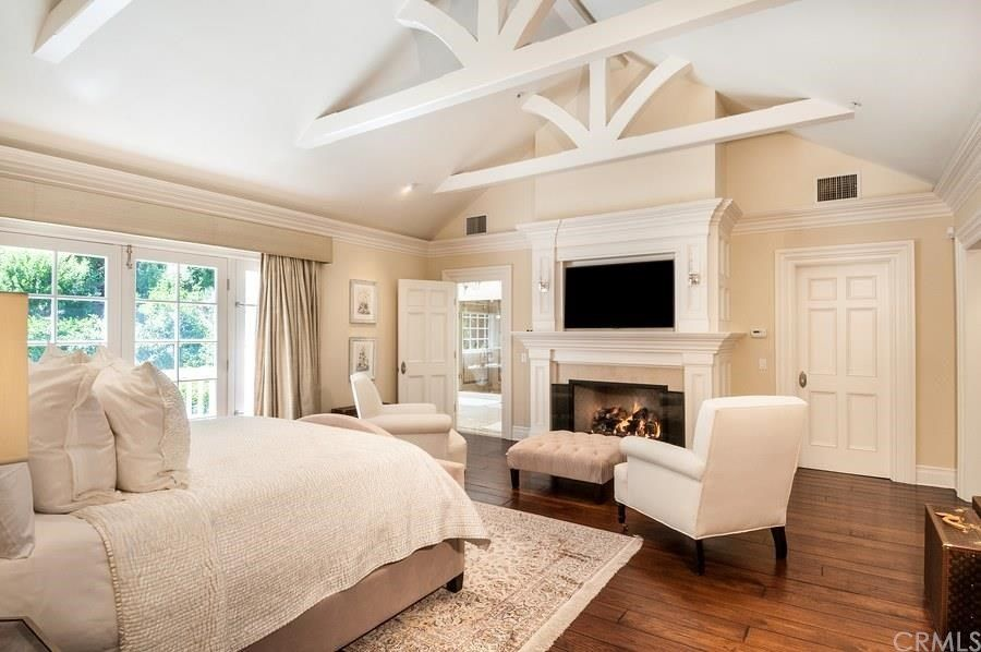 Traditional master bedroom with stone fireplace hardwood floors crown molding carpet Master bedroom with sloped ceiling