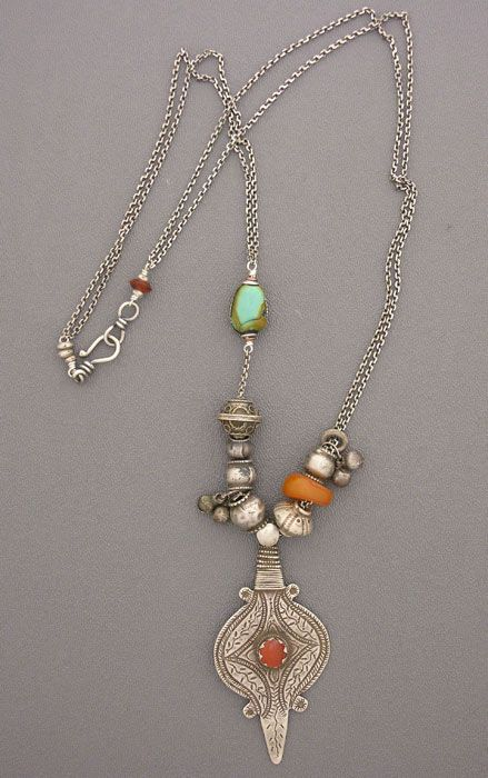 by Anne Holland |  A simple, long, beautiful necklace made with antique silver beads from  Afghanistan,an antique Tibetan bezelled turquoise bead, and an antique  Moroccan amber bead, all resting above an antique silver and carnelian  Afghani amulet. Tibetans believe that turquoise has strong protective and  beneficial medicinal properties, and that it is a living thing, not just a simple  stone. On a sterling silver chain, with a sterling silver hook and eye clasp. | Dorje Designs
