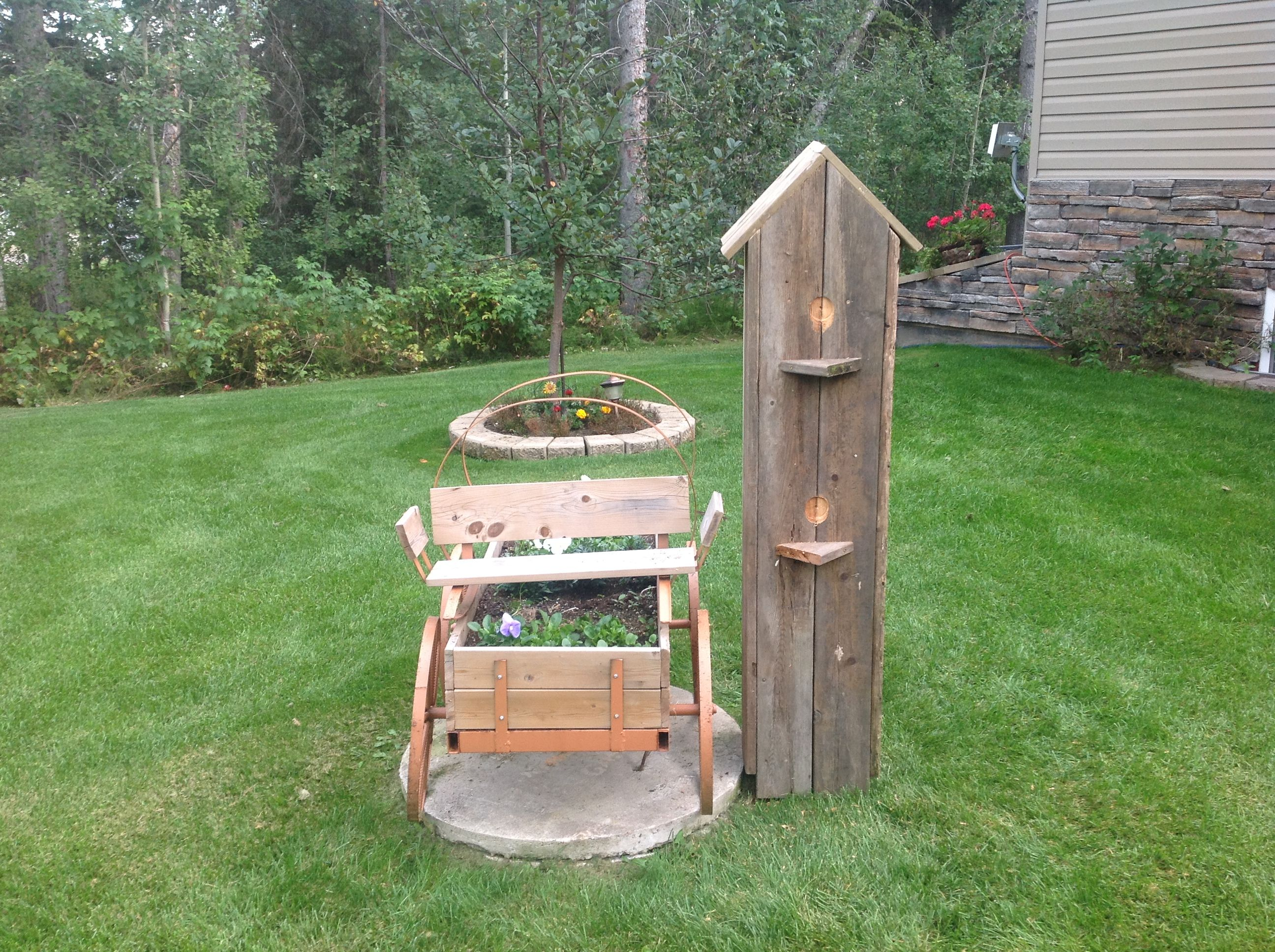 chuckwagon with flowers on a septic tank lid and a handmade birdhouse to cover the electrical