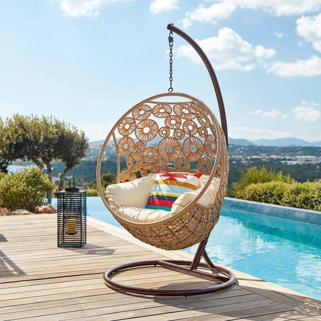 un fauteuil oeuf suspendu pour le jardin en osier avec un joli motif de rosaces au bord de la piscine