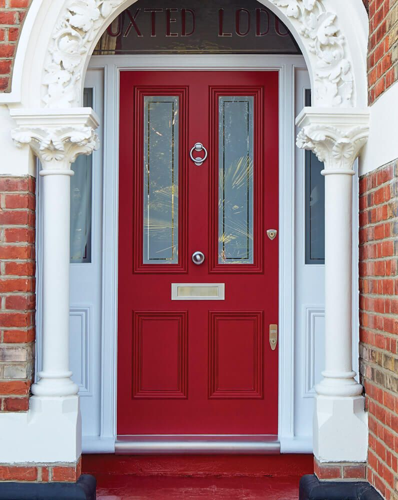 Set inside an ornate pillared stone porch, this elegant red front door and frame with part glazed panelling creates an impressive welcome. The vibrant paintwork is a bold finishing touch to this beautifully crafted Victorian door. #victorianfrontdoors