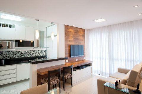 A pequena sala integra cozinha, jantar e estar. Os tons claros escolhidos ajudam a deixar o ambiente clean, favorecendo a sensação de maior amplitude. A madeira entra como elemento de conforto visual e aconchego. Projeto de Maristela Lima Bernal.