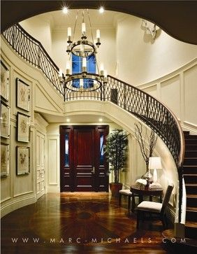 Curving stairs with wood rails and iron casings ascending from a large well decorated entry hall.