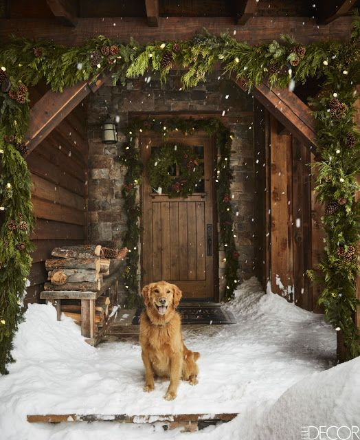 The gorgeous front door entry decorated for Christmas of a rustic ski house in Montana designed by Ken Fulk
