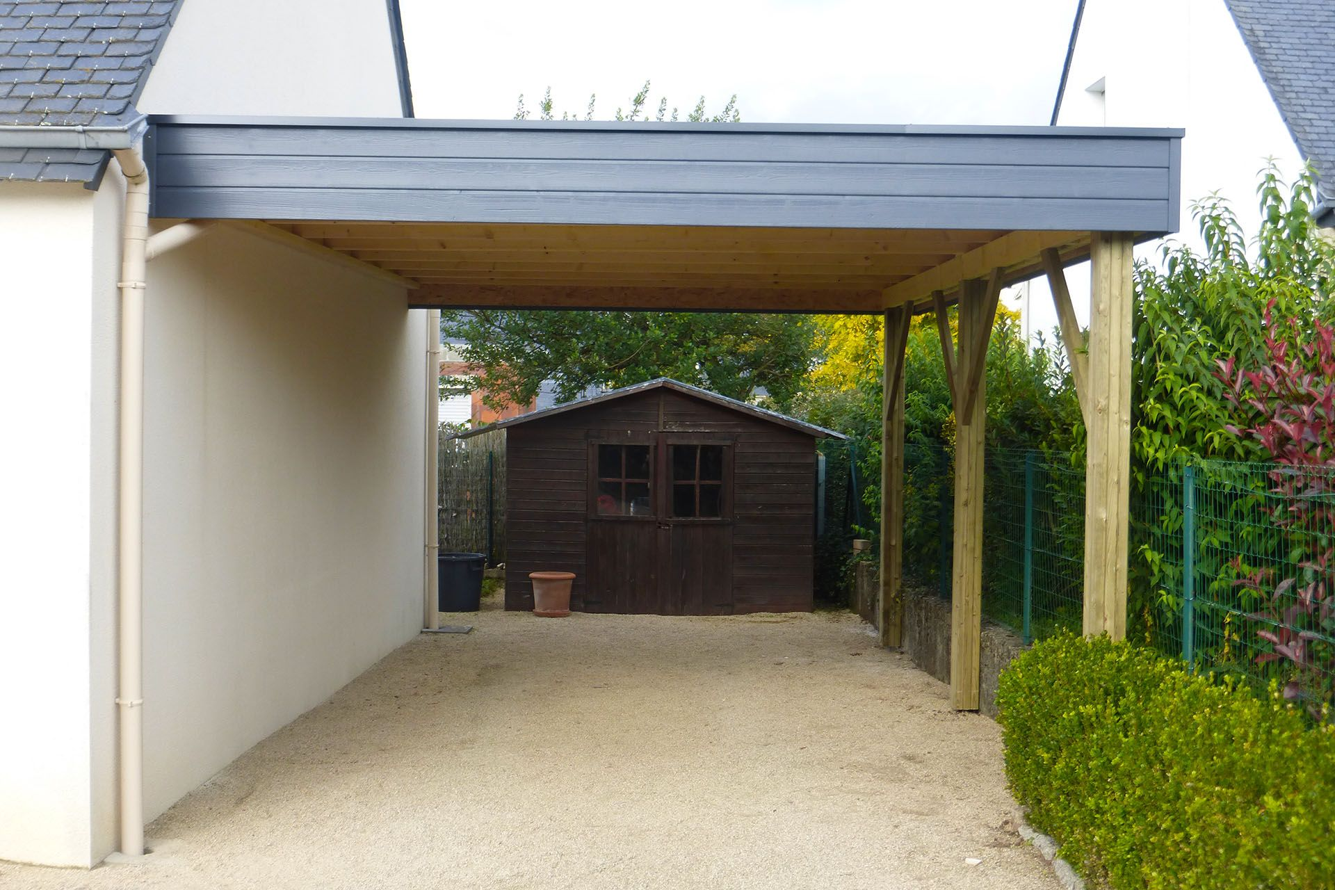 Grand carport en clin adossé à une maison traditionnelle