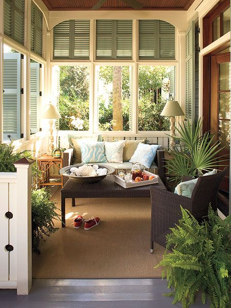 This traditional porch near Palmetto Beach, South Carolina, employs coastal-style architecture to give this new home old Southern charm with shutters that reach all the way to the ceiling. The folding shutters can be opened to let in light and air or closed for more privacy. The slats can be adjusted to let air circulate.