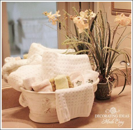 The Art Gallery Bathroom Decorating Ideas use a pretty floral container to hold towels in your guest bathroom