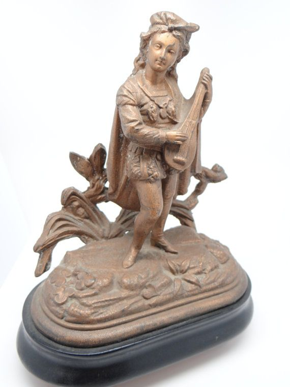 Wonderful old bronze painted Victorian spelter stature of a minstral on a wooden base. Young man playing a musical instrument standing on rocks with decorative back.