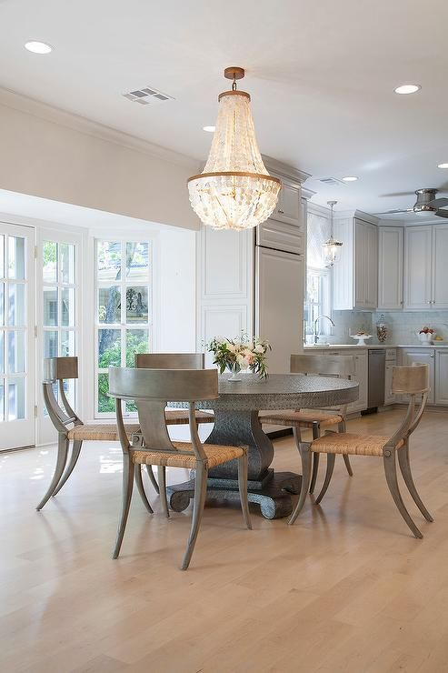Stunning Dining Room Features A Round Zinc Dining Table Lined With