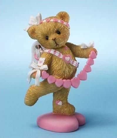 Precious Valentine's Day Cupid bear holds string of candy hearts, an arrow of love strapped to her back.