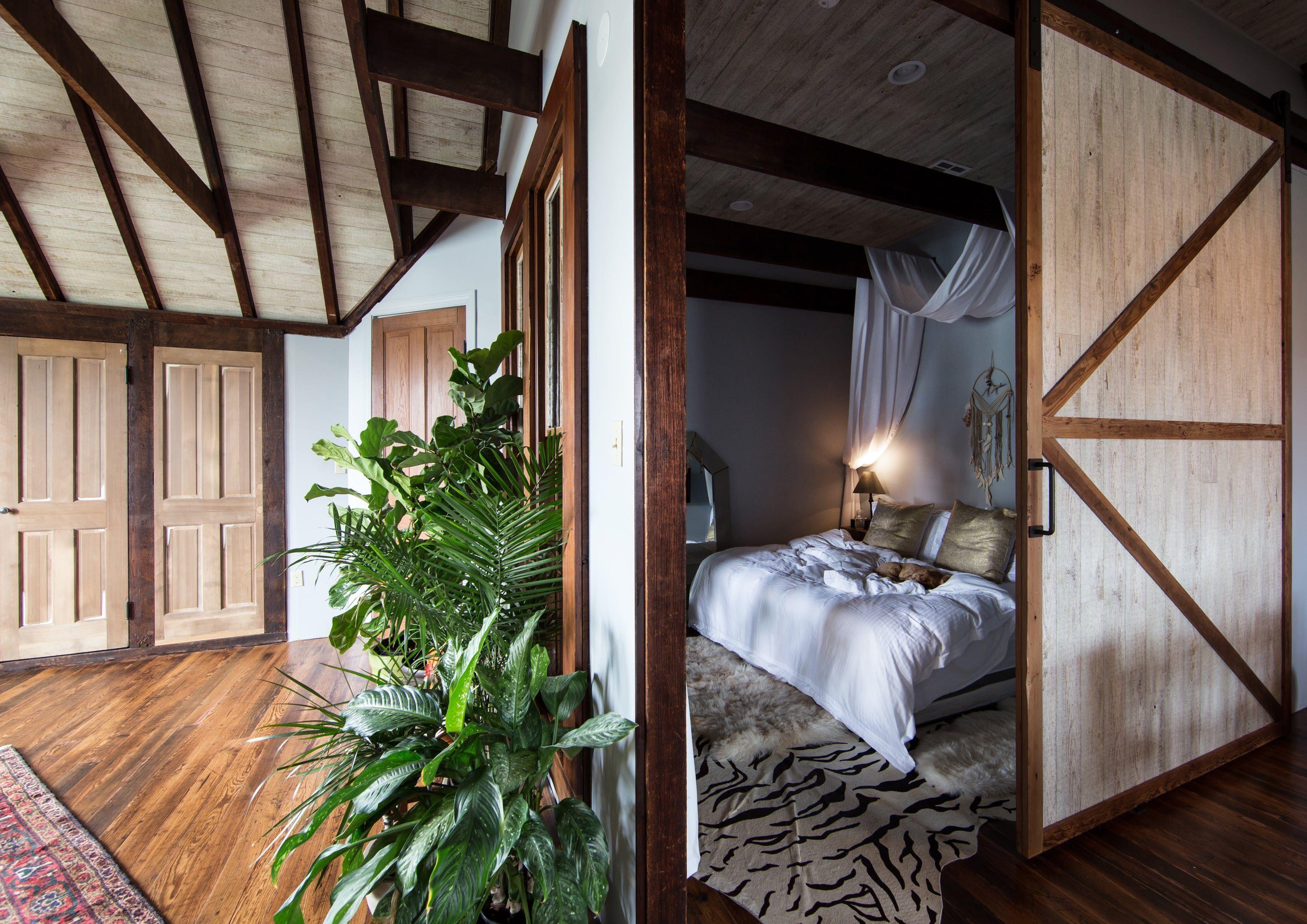 Melindaus bedroom is tucked away behind a sliding barn door and a