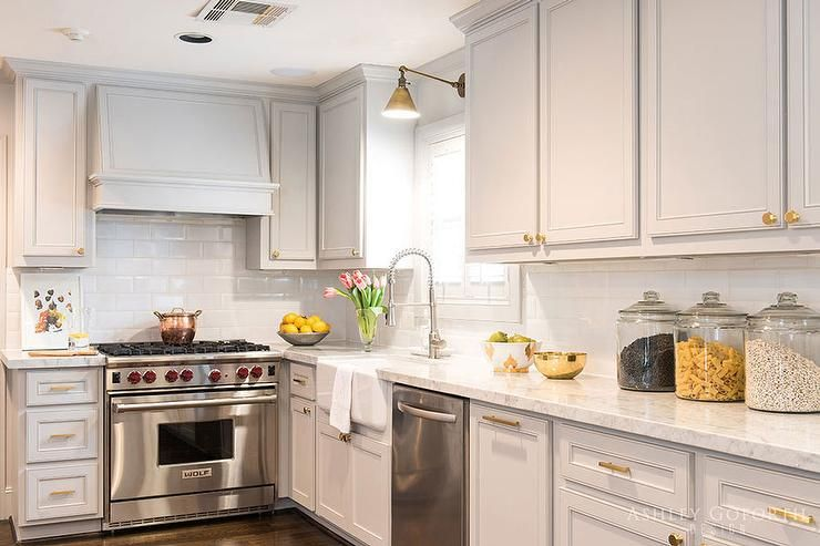 L shaped kitchen features pale grey cabinets adorned with brass ...