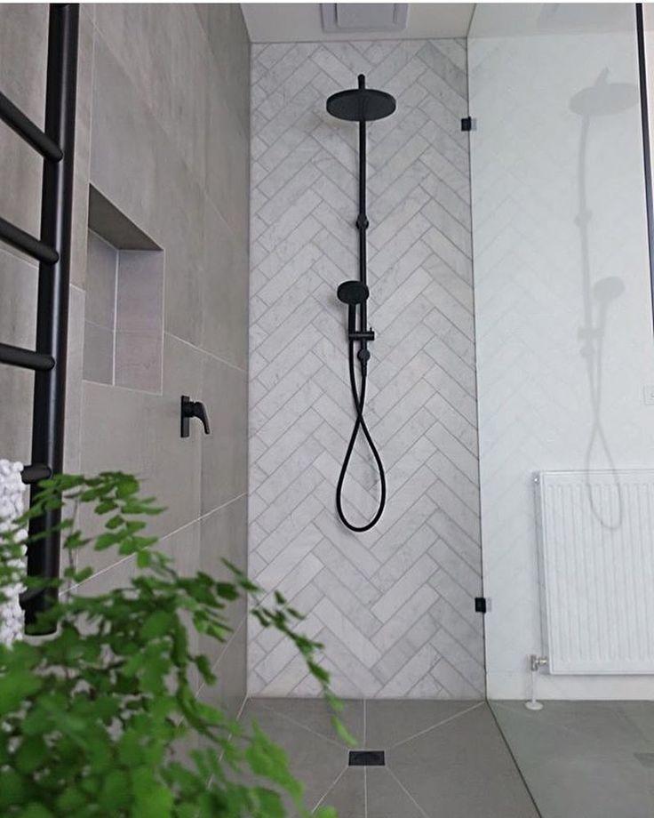 Photo of Le plancher et un mur d'une douche en tuile d'allure béton mat et un mur en…