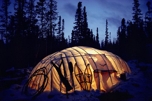 The light from a kerosene lamp illuminates a Cree winter tent in boreal forest. Quebec, Canada.