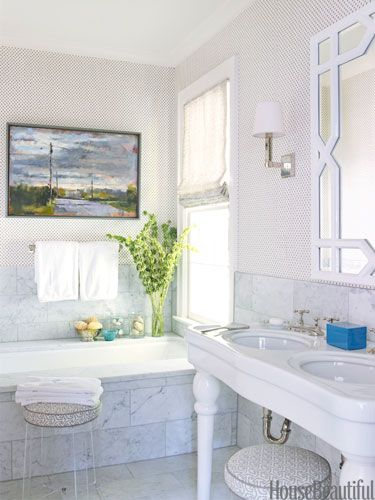 designer Lindsey Coral Harper updated the fixtures, added Carrara marble tiles, and had the tub glazed from beige to white