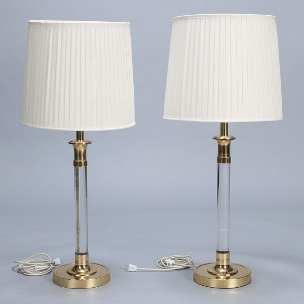 "Pair Tall Mid Century Lucite and Brass Table Lamps --- Circa 1960s tall lucite and brass table lamps have brass pedestal bases, substantial supports, brass fittings and vintage shades. Updated electrical wiring for US standards. One lamp base is approximately 1"" taller than the other - it appears that the brass fittings on the the taller lamp are taller by approximately 1/2"" at base and top.   ---  Item:  5728 --- Retail Price:  $3995"