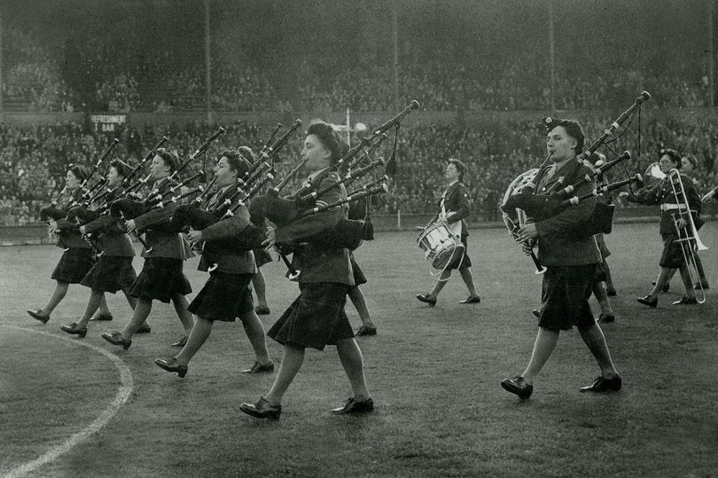 Mary Munro (right) eyes the camera as she plays the bagpipes during World War 2