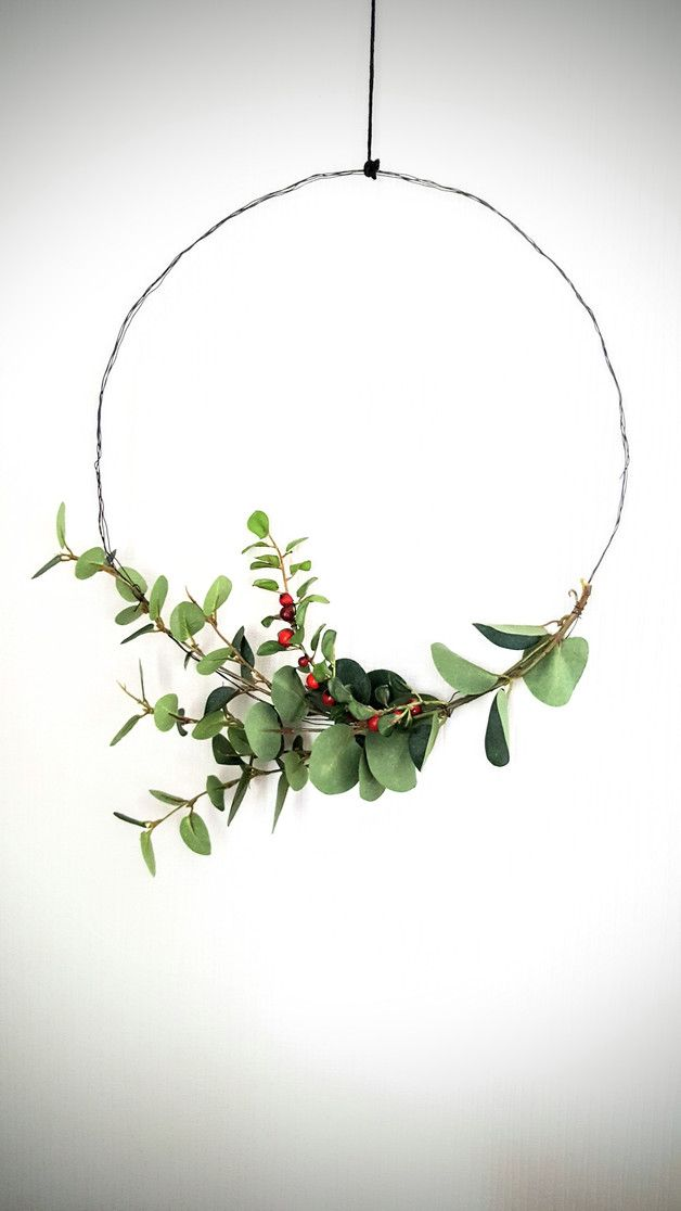 Photo of Scandinavian Christmas decoration with wire circle and eucalyptus / wire circle with …